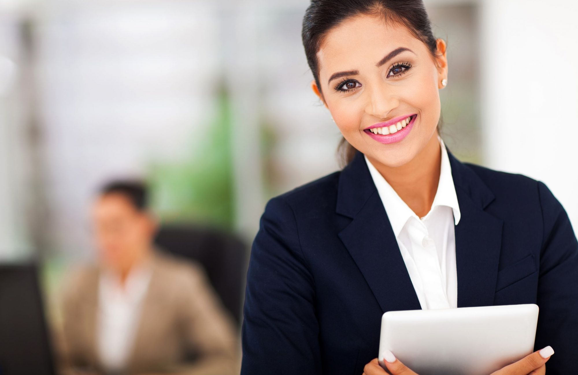 18983658 - young attractive business woman holding a tablet computer