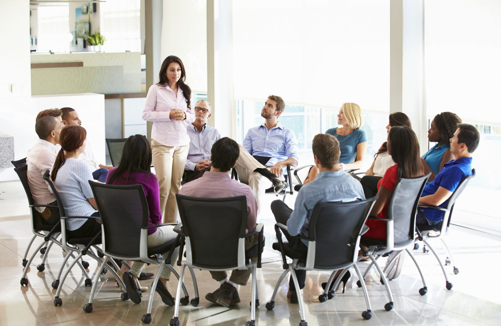 31047574 - businesswoman addressing multi-cultural office staff meeting