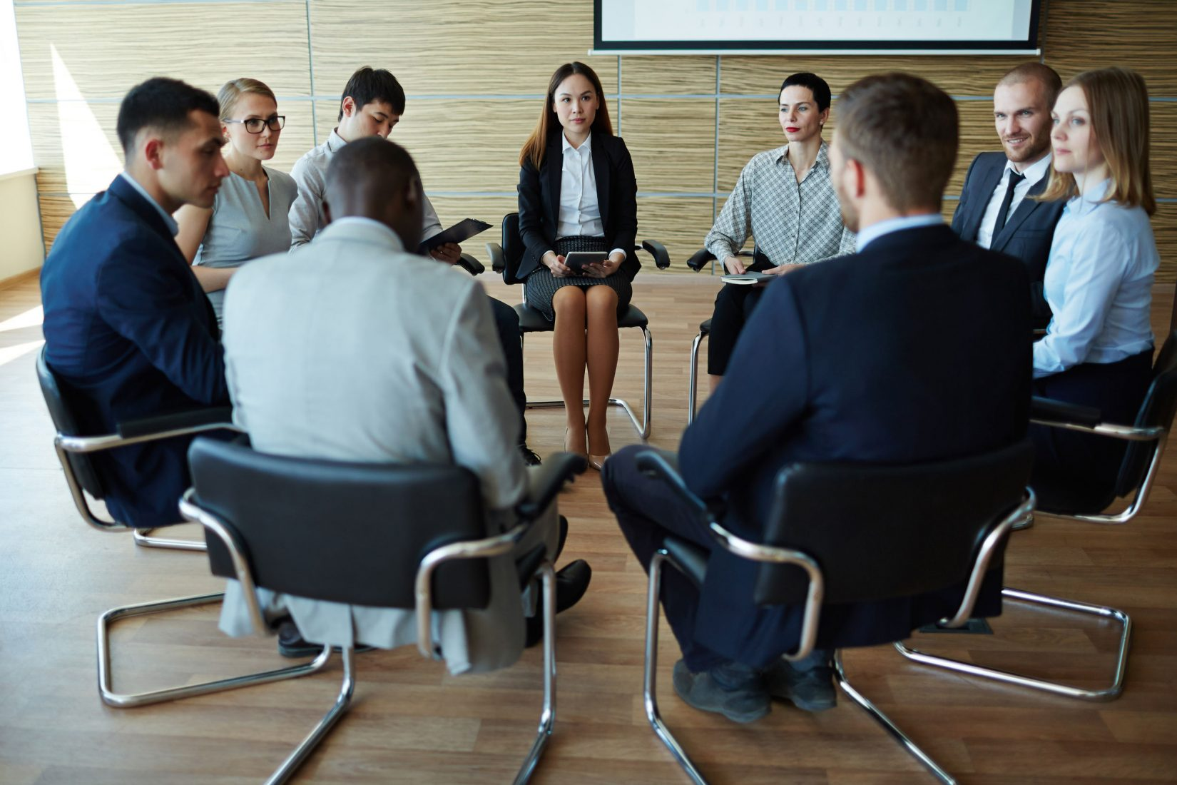 59971519 - businesspeople seated in circle at company seminar