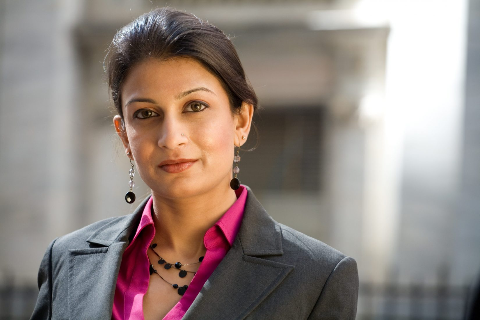 Friendly Indian Businesswoman Wearing a Suit in City Setting