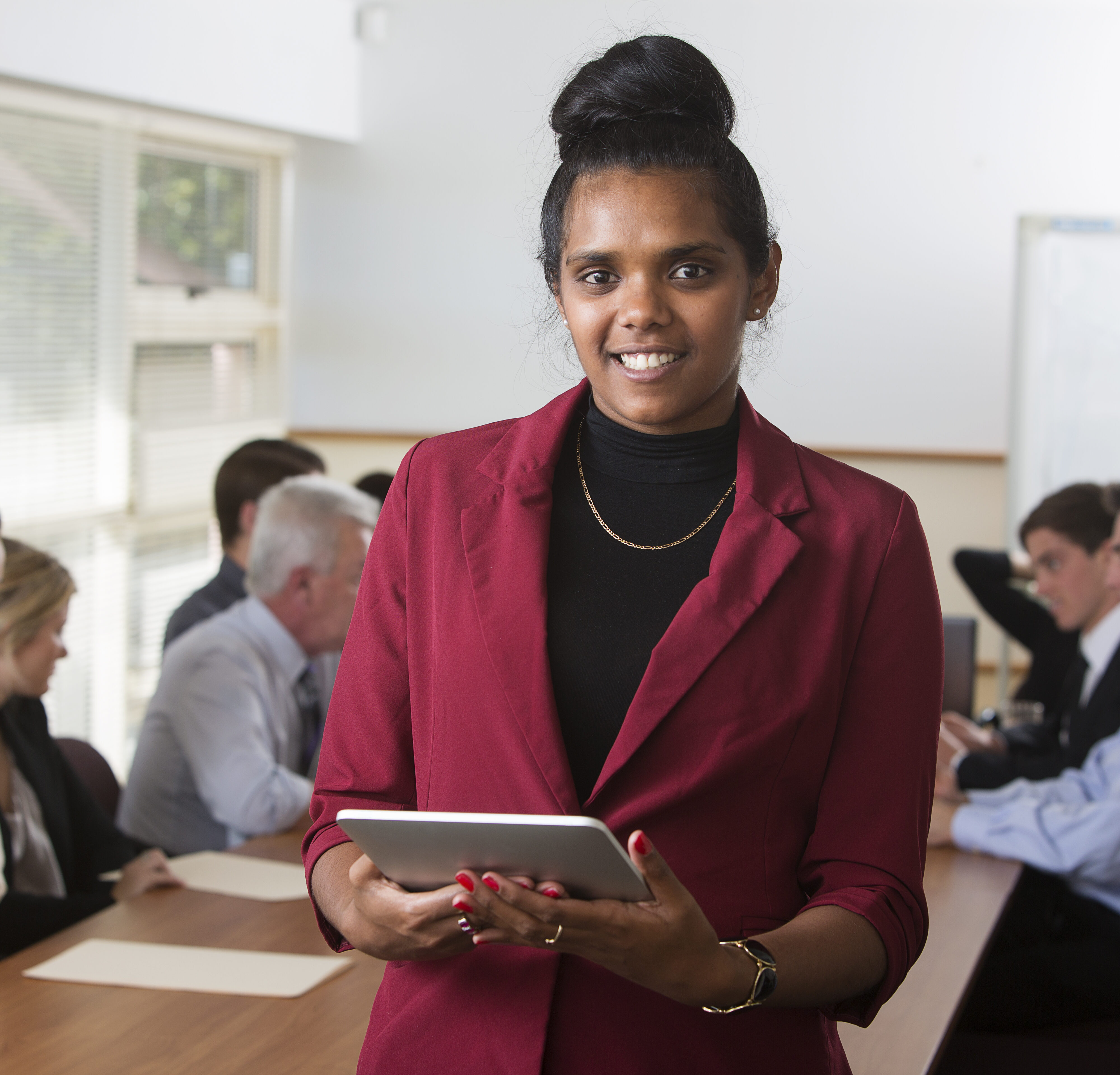 Austrtalian aboriginal woman using a tablet computer in a staff meeting or boardroom