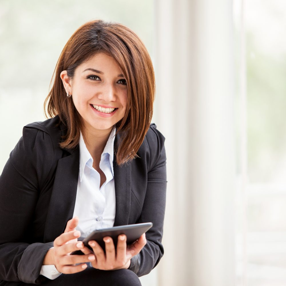 Pretty brunette on a suit working social networking on a tablet computer and smiling