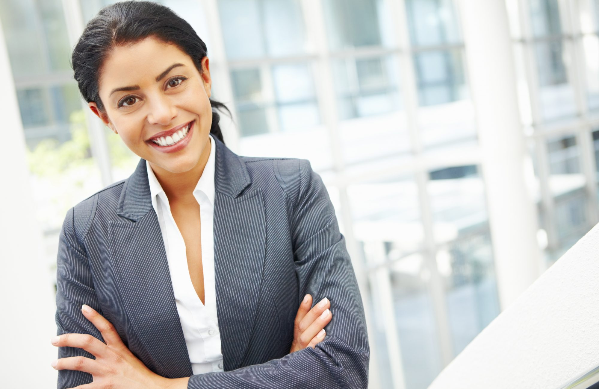 Portrait of an attractive female executive smiling with arms crossed at the workplace - copyspace