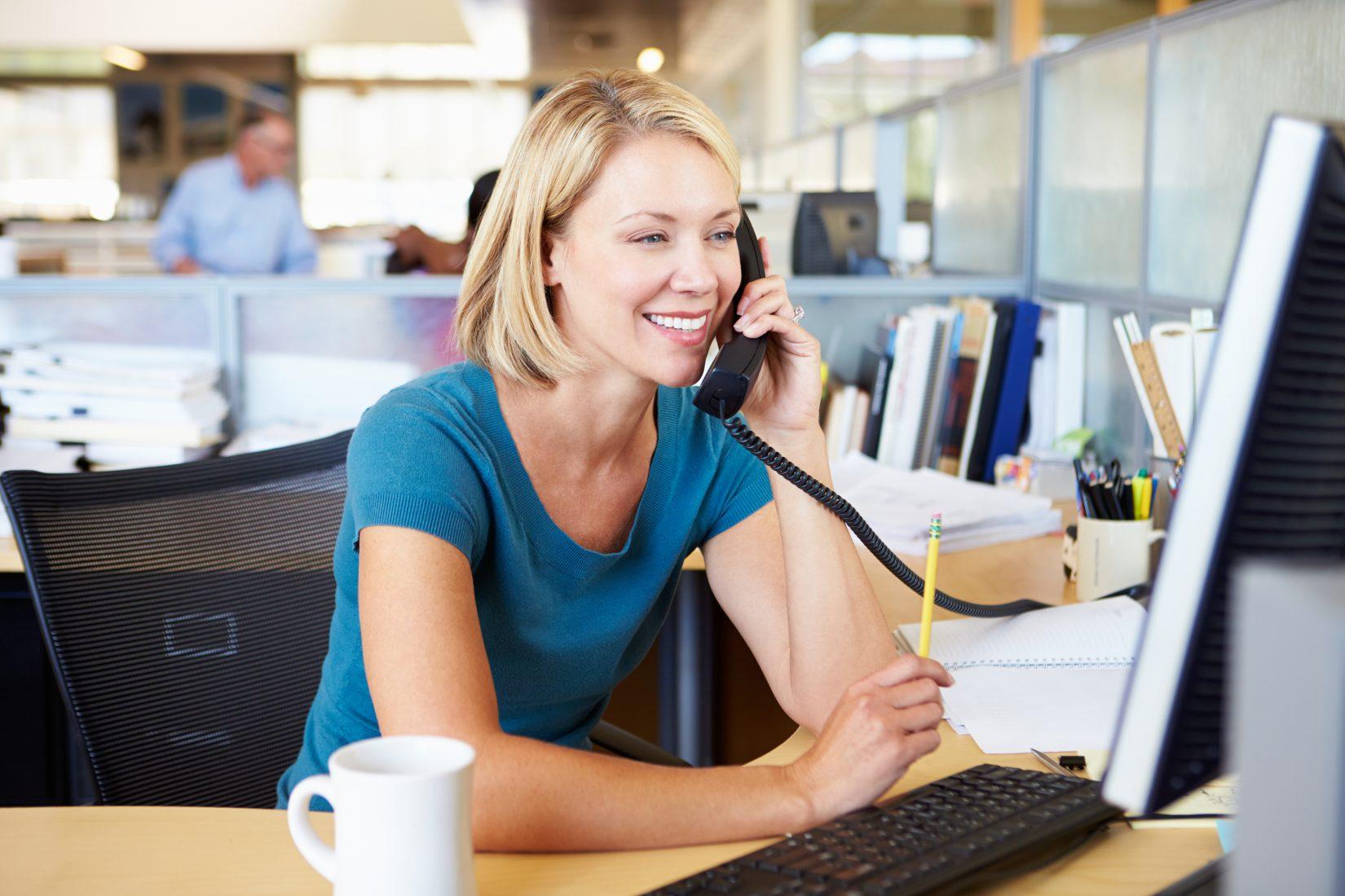 Woman On Phone In Busy Modern Office In Smart/Casual Dresswear