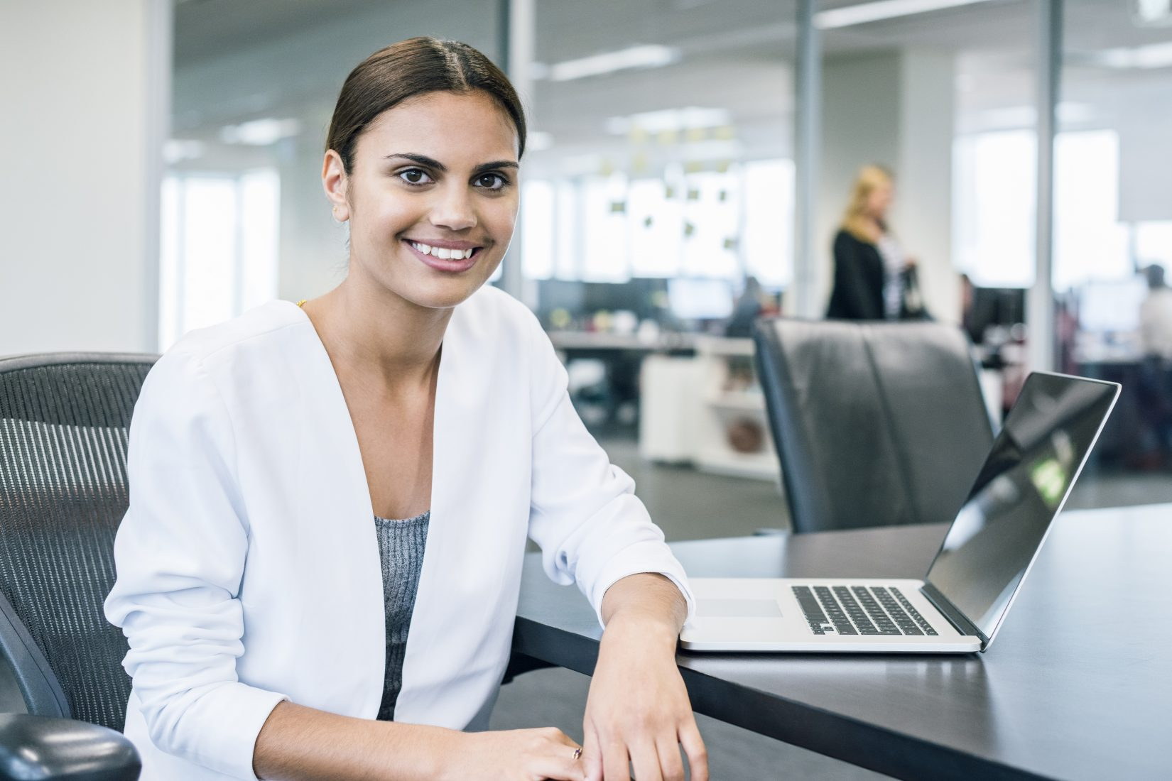 Young ethnic aboriginal Australian businesswoman seated at meeting room table by laptop computer modern office. Portrait looking to camera of a female business professional in Australia.