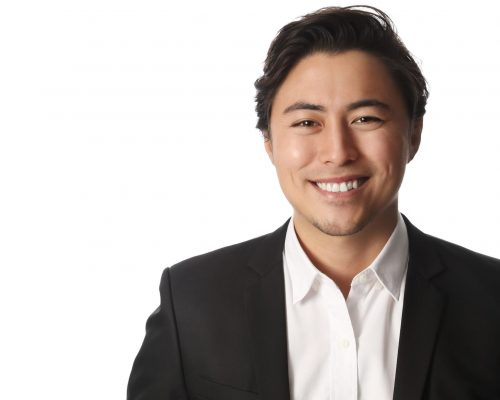 A young and professional businessman standing in front of a white background smiling looking at camera.