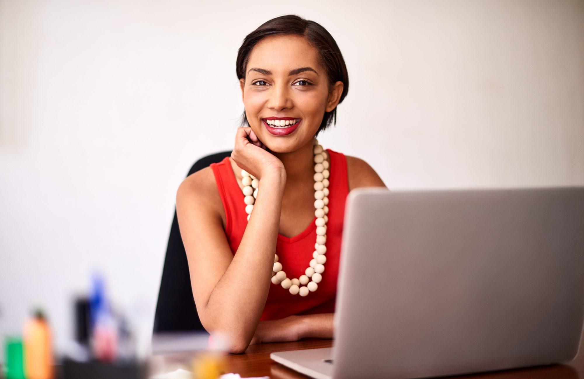 Portrait of a young woman working on a laptop in an office