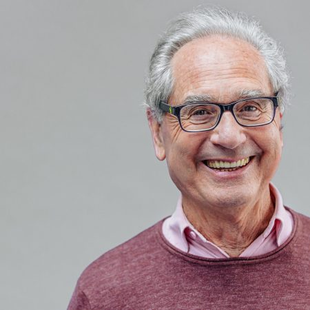 Portrait of a natural smiling, happy senior French businessman with glasses and smart casual, real people studio shot with copy space on gray background. XXXL