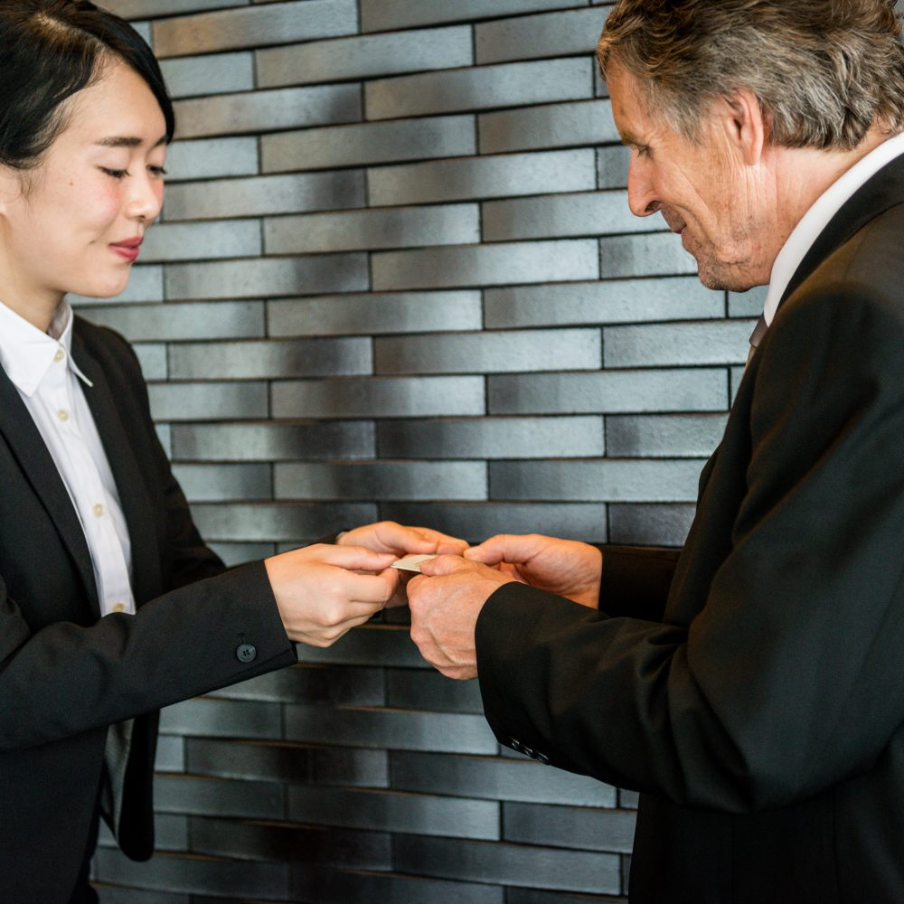 Happy senior Caucasian businessman and a young Japanese businesswoman/entrepreneur are exchanging their business cards, Kyoto, Japan, Asia. Office interior, copy space. Nikon D800, full frame, XXXL. iStocklypse Kyoto 2016.