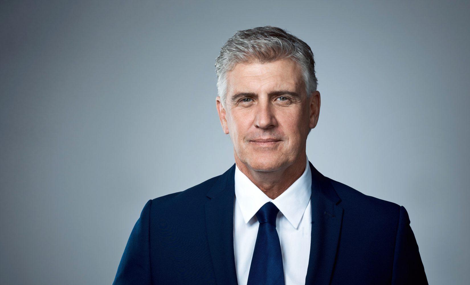 Studio portrait of a mature businessman posing against a grey background