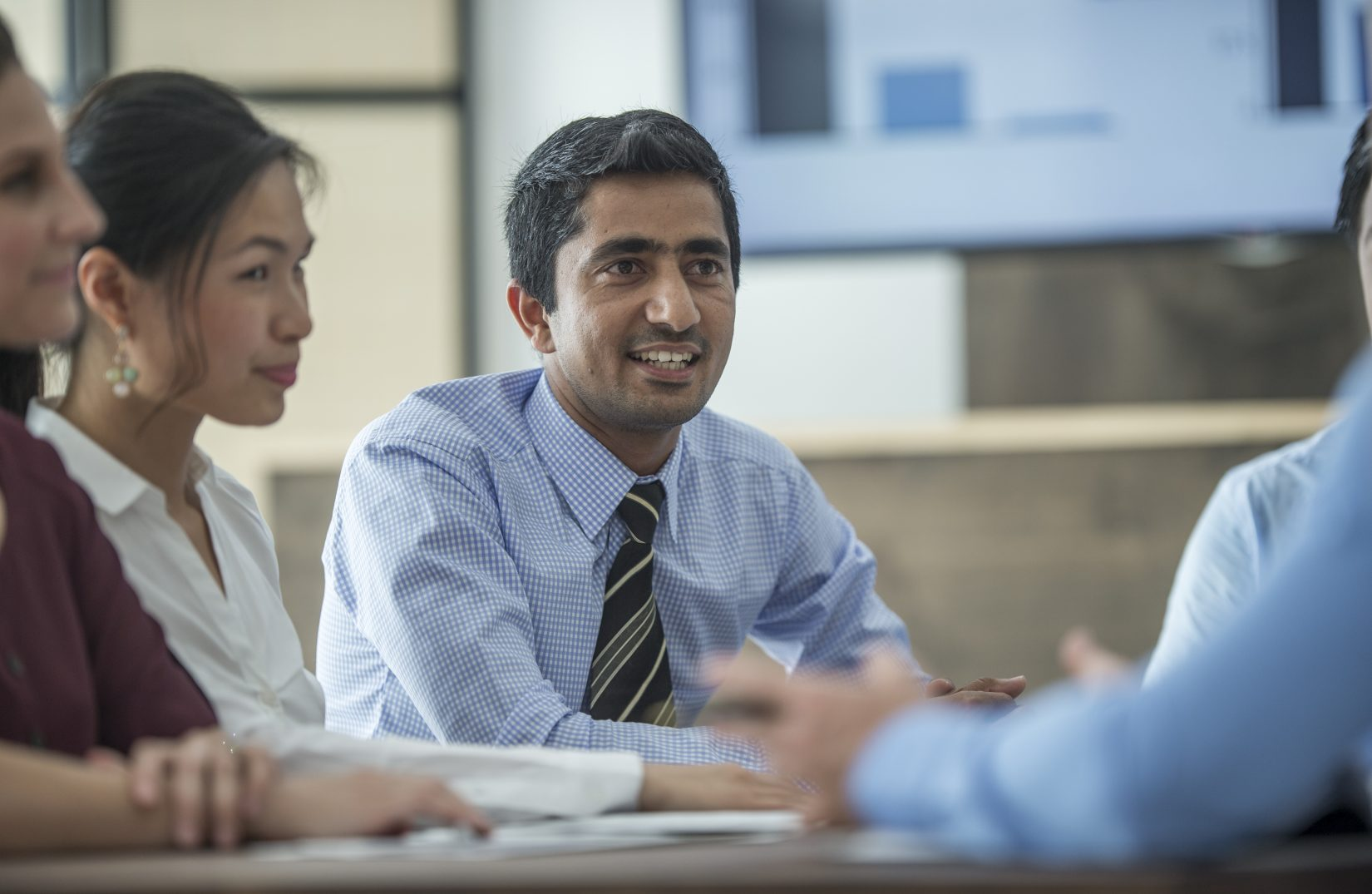 A multi-ethnic group of business professionals are working together in a boardroom corporate office.