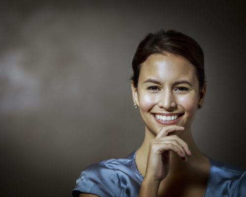 Portrait of happy businesswoman with hand on chin. Confident female professional is against grey wall. She is in formals.