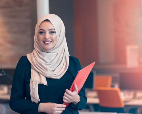 Arabian business woman holding a folder and talking on the phone isolated on white
