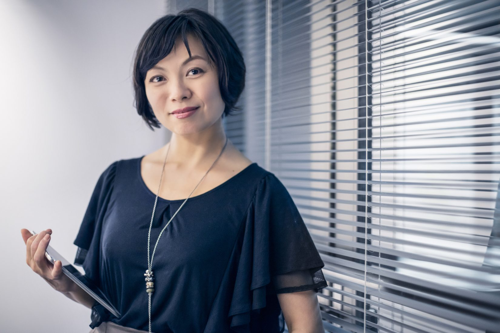 Portrait of mature businesswoman holding digital tablet by blinds. Confident female professionals is holding wireless technology. She is wearing formals in office.