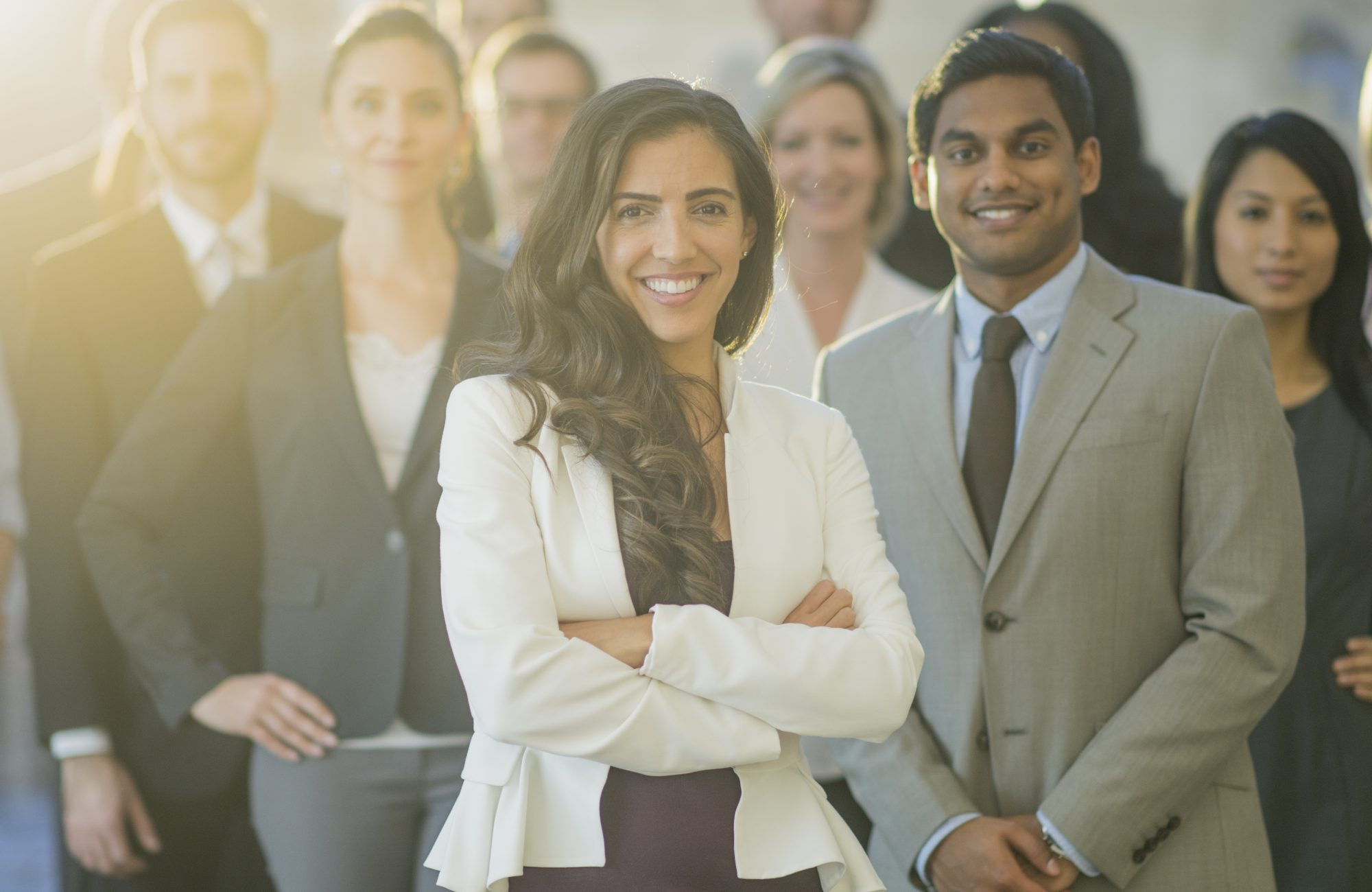 A group of professionals stand together for a portrait session. They are dressed in business wear that represents their occupations. A young woman stands in front.