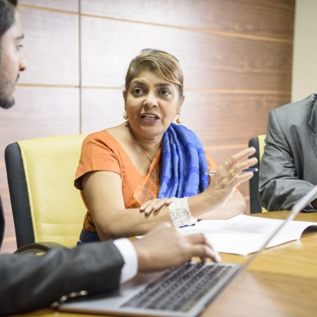 Mature woman explaining in office, man using computer in foreground, senior man listening to woman as she gestures towards colleague