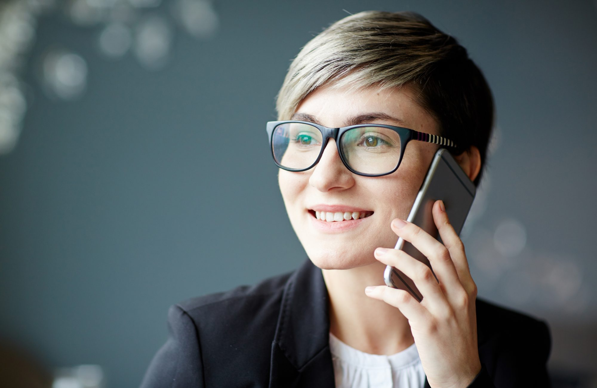 Pretty young businesswoman with cellphone talking to client