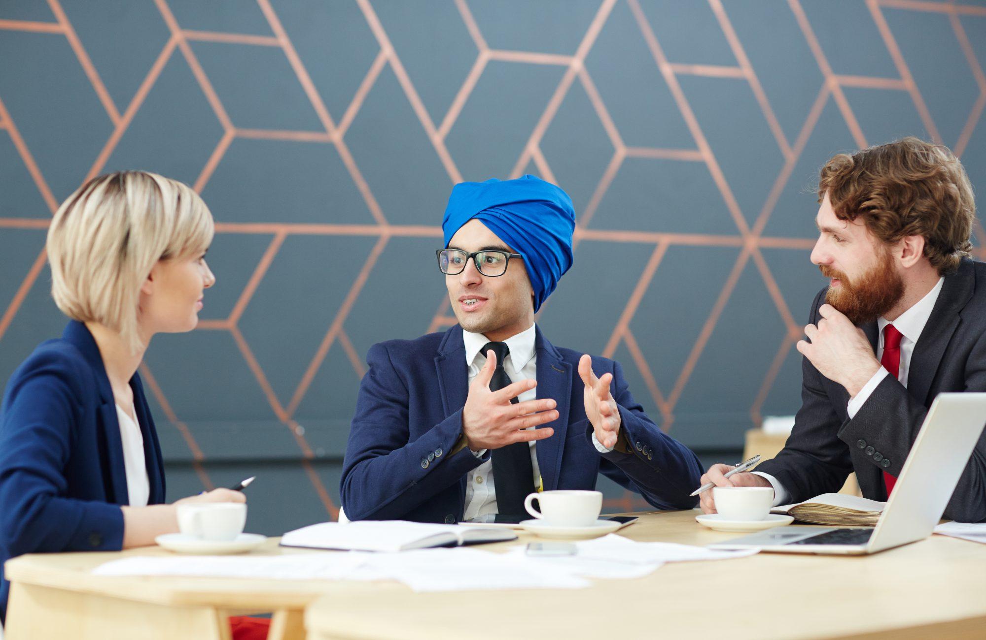 Arabian man in turban giving interview in tv-studio