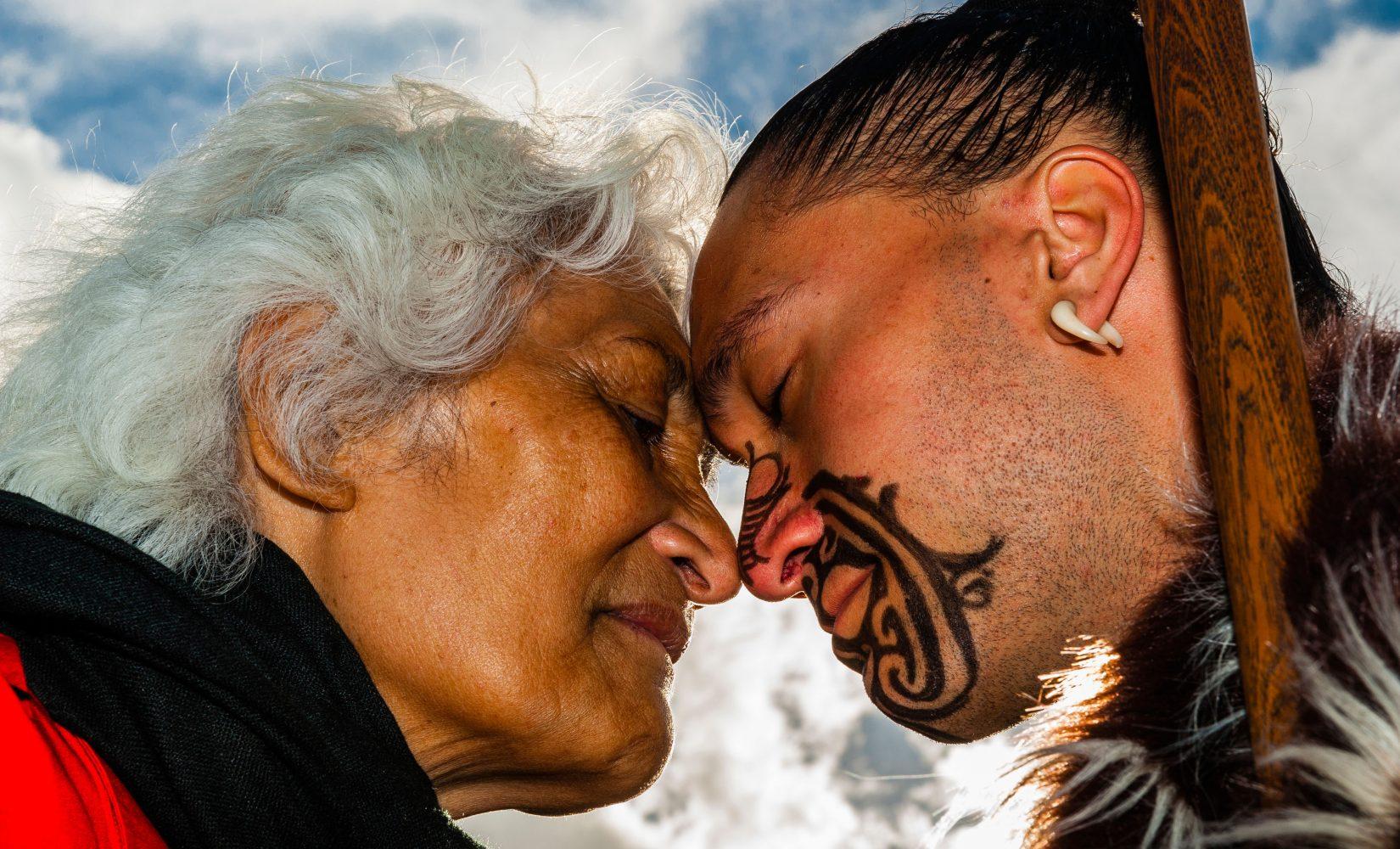 D72CNG A Maori man with ta moko (facial tattoo) and an elderly Maori woman doing hongi (traditional Maori greeting) , Te Puia (New Zealand Maori Arts & Crafts Institute), Rotorua, New Zealand